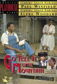 A black man and woman sit on a porch. The woman sits in a chair. The man, dressed in overalls, sits on the floor of the porch, reading a book