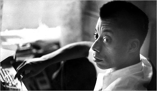 A black-and-white photo of James Baldwin at his desk, looking at someone or something out of frame. A typewriter and glass are just out of focus.