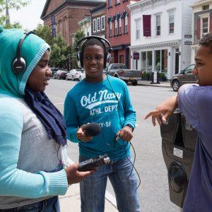 Three teens on a sidewalk. Two have audio equipment.