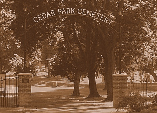 """The name """"Cedar Park Cemetery"""" spans the arch of the entry gate to a cemetery. Large trees occupy the middle ground, and tombstones the background."""